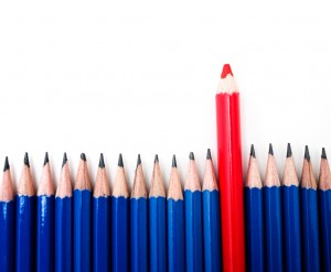 blaze your own trail - one red pencil standing above a group of blue pencils